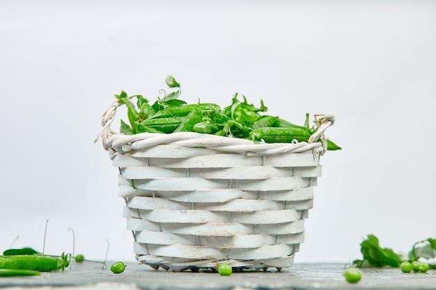 Белая корзина со свежим зеленым горошком на сером фоне.