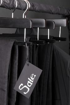 Множество черных брюк джинсов и куртка висят на вешалке