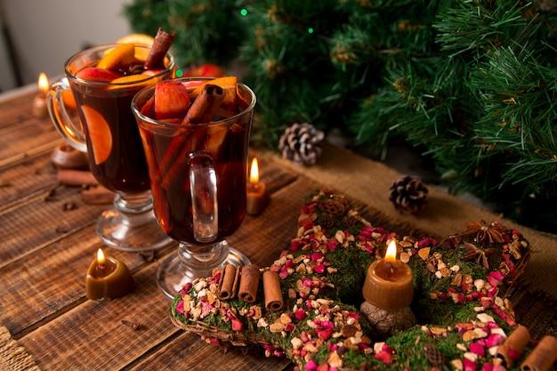 クリスマスのグリューワインと木製のテーブルの上のろうそく