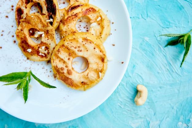 青の背景に白い皿にシナモンと焼きりんご。