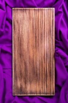 Деревянная разделочная доска на пурпурной ткани
