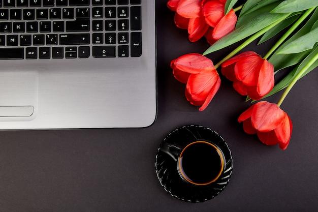 Рабочая область с ноутбуком, красными тюльпанами и черным кофе