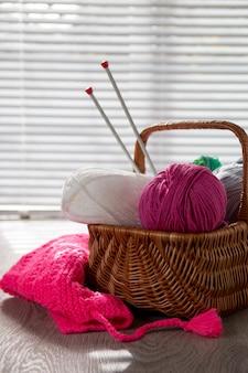 窓の光と木製の灰色のテーブルの上のバスケットに糸と編み針のボール。手作り。