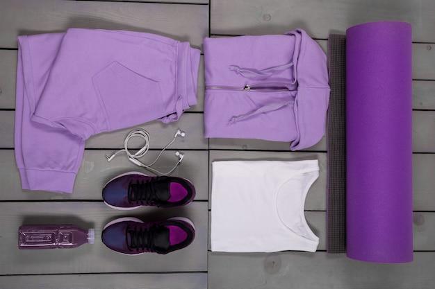 女性のスポーツ用品。紫のスポーツパンツ、靴、スーツ、マット、水のボトルの白いヘッドフォン