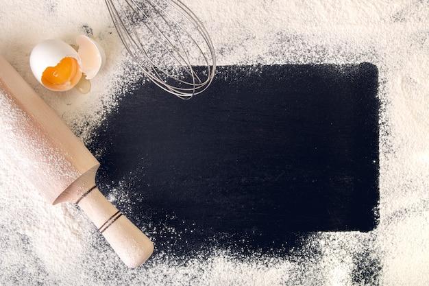黒い背景に麺棒、小麦粉、卵の周りのスペースをコピーします。上面図。フレーム。