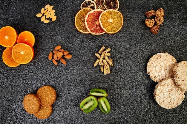 Разнообразные овсяные батончики, рисовые чипсы, миндаль, киви и сушеный апельсин