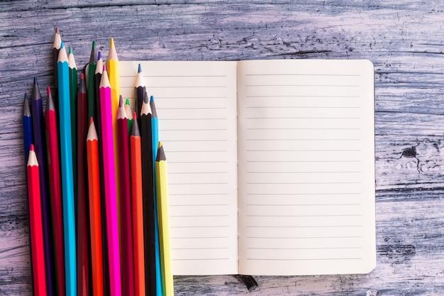 木製の背景に注意に近い色鉛筆。上面図。コピースペース。