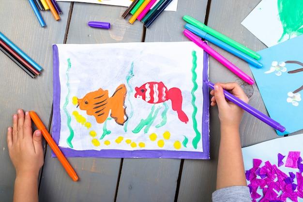 鉛筆画の絵と子供の手のトップビュー
