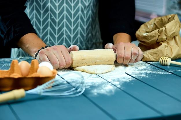 Бейкер готовит свежее тесто со скалкой на кухонном столе