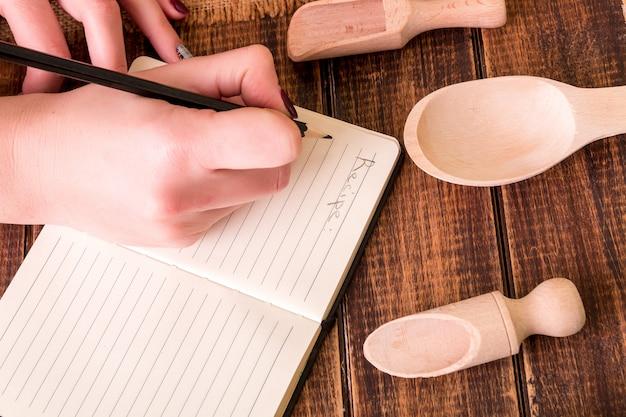 Рука женщины написать рецепт в кулинарной книге. книга для рецепта вокруг посуды на деревянных фоне.