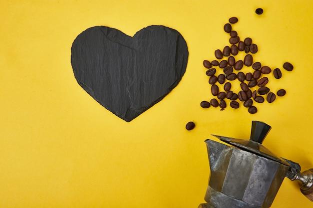 Плоская планировка кофеварки и кофейных зерен на желтом фоне.