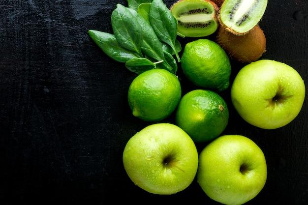 スムージーの材料。黒の木製の背景に緑の果物。リンゴ、ライム、ほうれん草、キウイ。デトックス。健康食品。上面図。コピースペース。