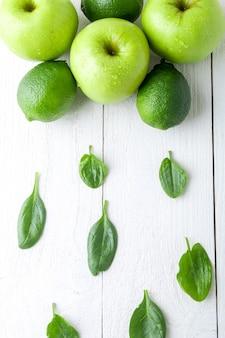 白い木製の背景に緑の果物。リンゴ、ライム、ほうれん草。デトックス。健康食品。上面図。コピースペース。