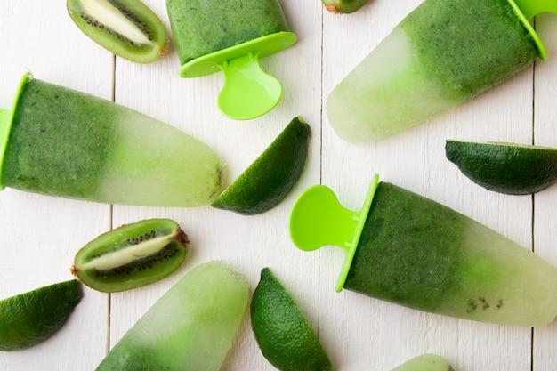 白い木製の背景に緑の自家製アイスクリーム。キウイとライムのフルーツアイス。上面図。