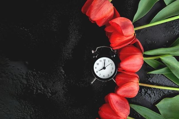 赤い花束の花束に近い黒い目覚まし時計。母または女性の日。グリーティングカード。おはようございます。コピースペース。春。