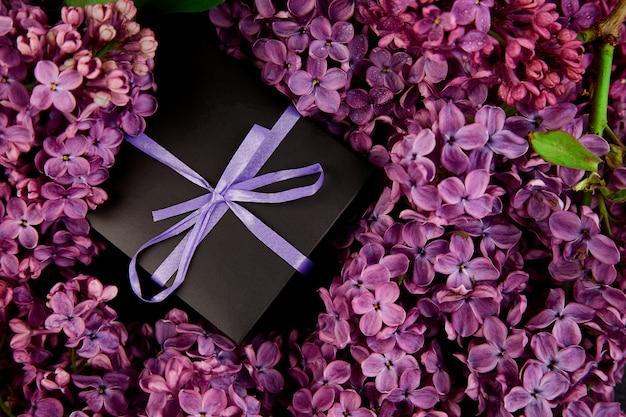 黒の小さなギフトボックスは、紫のリボンに天然のライラックを巻き付けました。