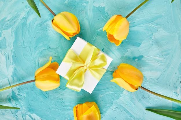 Подарочная коробка с желтой лентой возле тюльпана
