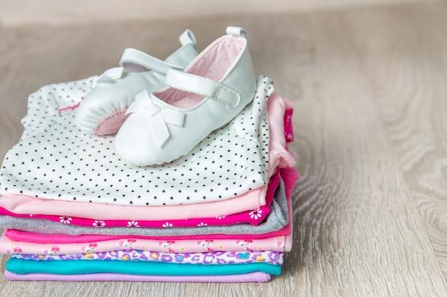灰色の木製の背景の上に靴と折り畳まれたピンクと白のボディースーツ。新生児のおむつ。幼児服のスタック。子供服。コピースペース。