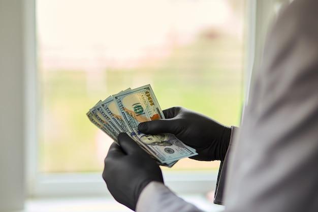 Укомплектуйте личным составом держать доллары денег в руке в черных медицинских перчатках.