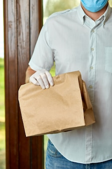 Курьер доставляет покупки онлайн до двери во время эпидемии коронавируса