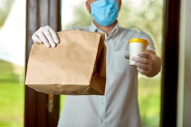 Курьер, курьер в защитной маске и медицинских перчатках доставляет еду на вынос, коронавирус