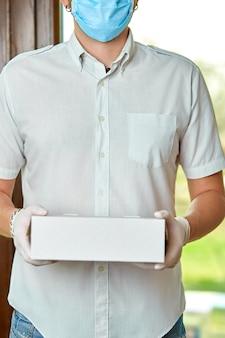 Курьер, курьер в медицинских латексных перчатках и маске безопасно доставляет покупки онлайн во время коронавируса