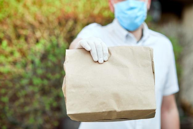 医療用ラテックス手袋を着用した宅配便の配達員が、コロナウイルスの流行中に、茶色の紙袋に入ったオンライン購入品をドアに安全に配達します