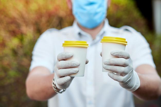 Доставка человек в защитной маске и перчатках, на вынос чашку кофе во время эпидемии коронавируса.