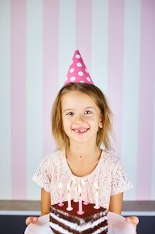 誕生日ピンクの帽子、キャンドルでチョコレートの誕生日ケーキで笑っている金髪少女。子供は彼女の誕生日を祝います。お誕生日おめでとうございます。