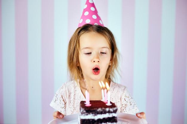 自宅で彼女の誕生日パーティーで誕生日チョコレートケーキのろうそくを吹きピンクの帽子の少女。肖像画の誕生日の子供。