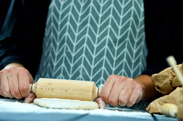 Руки пекаря готовят свежее тесто скалкой на кухонном столе