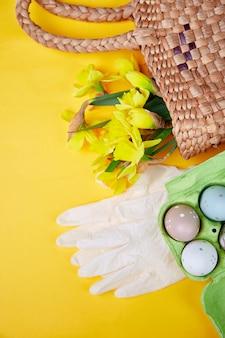 コロナウイルスイースターシンボル卵と水仙の花の保護医療用手袋、コロナウイルスの流行、検疫によるイースター休暇の概念の近くのバスケット