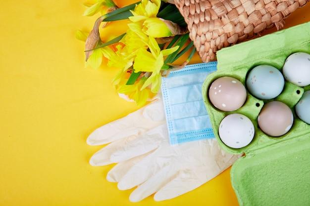 コロナウイルス検疫でのイースター成分のフラットレイ。イースターシンボルの卵と水仙花の保護医療マスクと手袋の近くのバスケット
