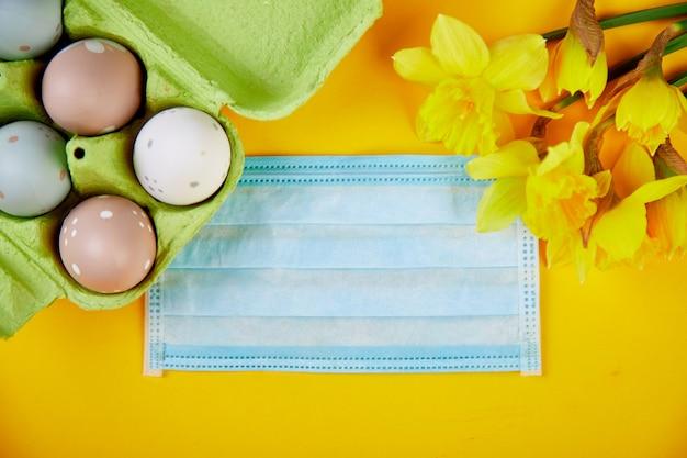 コロナウイルス検疫でのイースター成分のフラットレイ。イースターのシンボルの卵と水仙の花保護医療マスクの近く