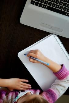 ノートブックで家で勉強して、宿題をしている認識できない女子高生。オンライン教育の遠隔学習。コロナウイルスホームスクールのコンセプト、検疫。上面図。