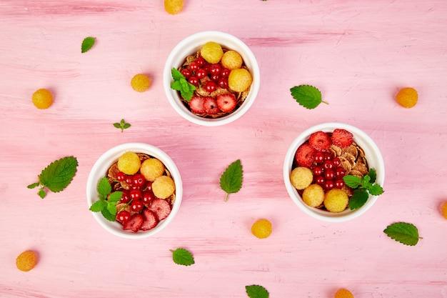 白いボウルで健康的な朝食。新鮮なグラノーラ、ミューズリー、またはベリー入りシリアル