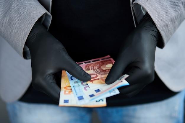黒の医療用手袋で手にお金のユーロの財布を保持している男。コロナウイルス危機。お金を節約。世界危機
