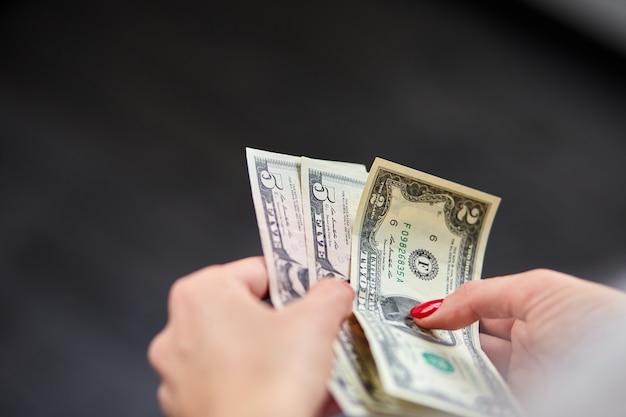 Женщина держит в руках деньги. экономика и финансовые рынки затронуты коронавирусом. экономить деньги.