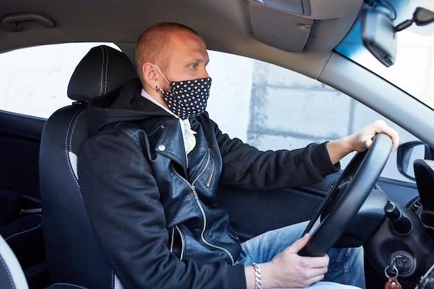 Человек с защитной маской приехал на машине на карантин пандемии коронавируса
