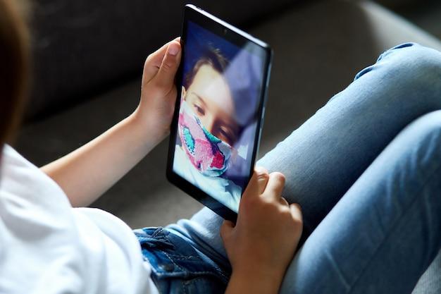 自宅でマスクの子少女がタブレット会議、オンライン通話の友人とビデオを話す