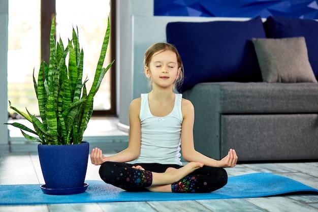 Маленькая девочка медитирует в позе лотоса с закрытыми глазами