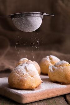 アイシング砂糖プロフィットロールで飾るプロセス。素朴なスタイル。
