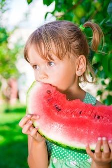 屋外の公園で夏の時間に大きなスライススイカと幸せな金髪少女。