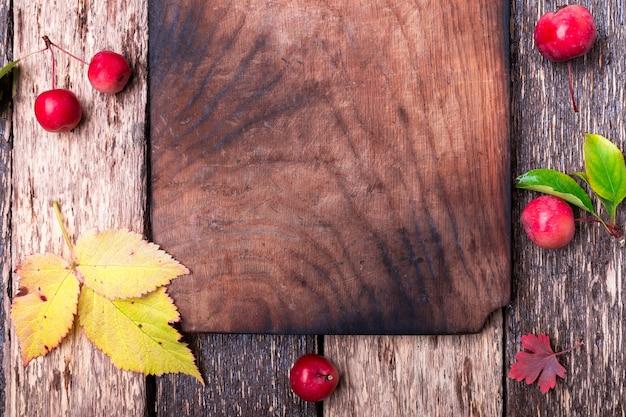空のまな板の周りの葉と小さなリンゴ