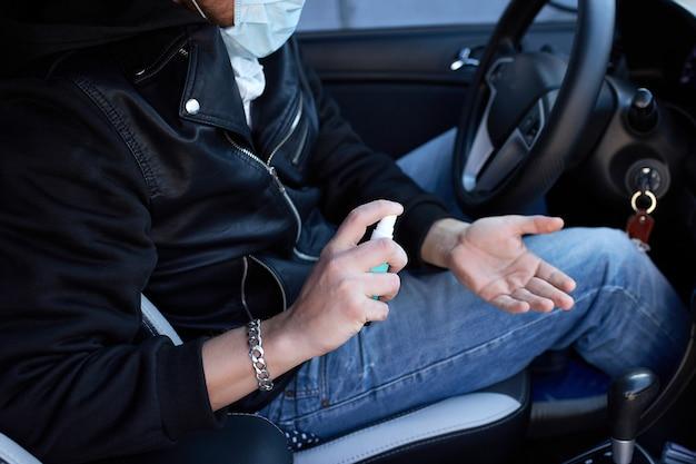 Человек в защитной маске сидит в машине, опрыскивая руки антибактериальным дезинфицирующим спреем для профилактики коронавируса