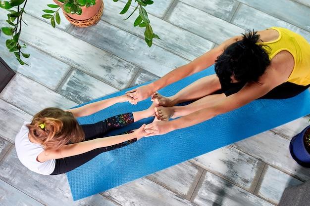 Мать или бабушка и ее дочь делают гимнастику вместе дома.