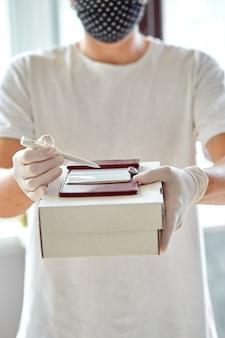 医療用ラテックス手袋の配達員である宅配便業者は、コロナウイルスの流行中にオンライン購入を安全に配達します。