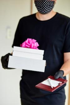 宅配便業者の非接触型配送プレゼント、コロナウイルスの流行中のギフトボックス。