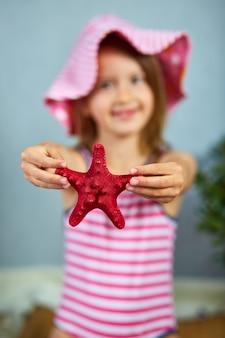 ヒトデを保持しているピンクの帽子をかぶっている笑顔の女の子。