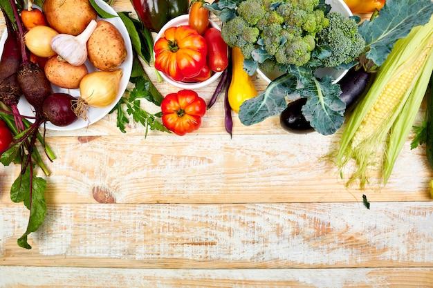 木製の背景に健康的な食事のためのさまざまな野菜。